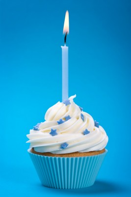 Cupcake with White Icing, Blue Paper, and Candle