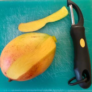 Mango on cutting board with peeler